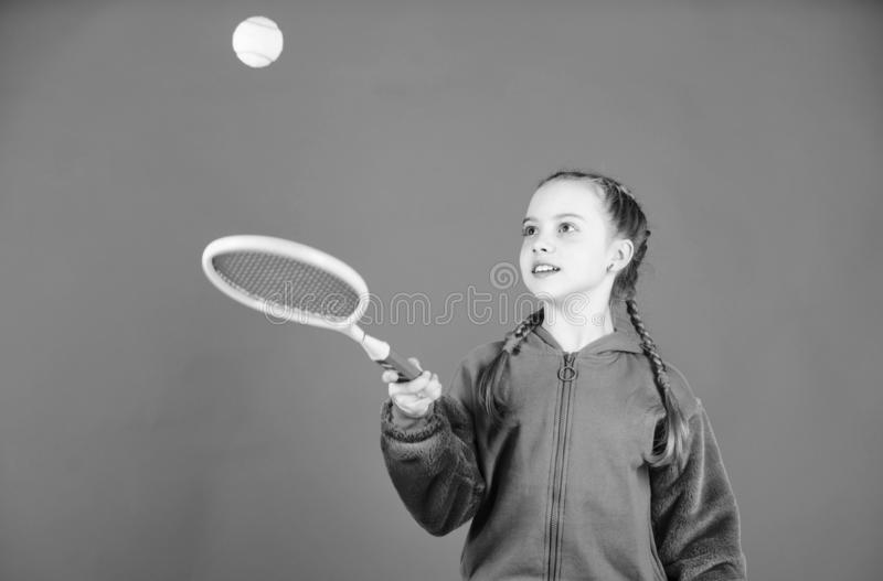 Girl adorable child play tennis. Practicing tennis skills and having fun. Athlete kid tennis racket on blue background. Active leisure and hobby. Tennis sport royalty free stock photography