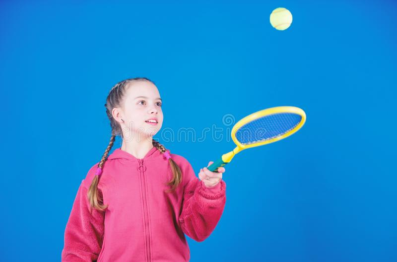 Girl adorable child play tennis. Practicing tennis skills and having fun. Athlete kid tennis racket on blue background. Active leisure and hobby. Tennis sport royalty free stock images