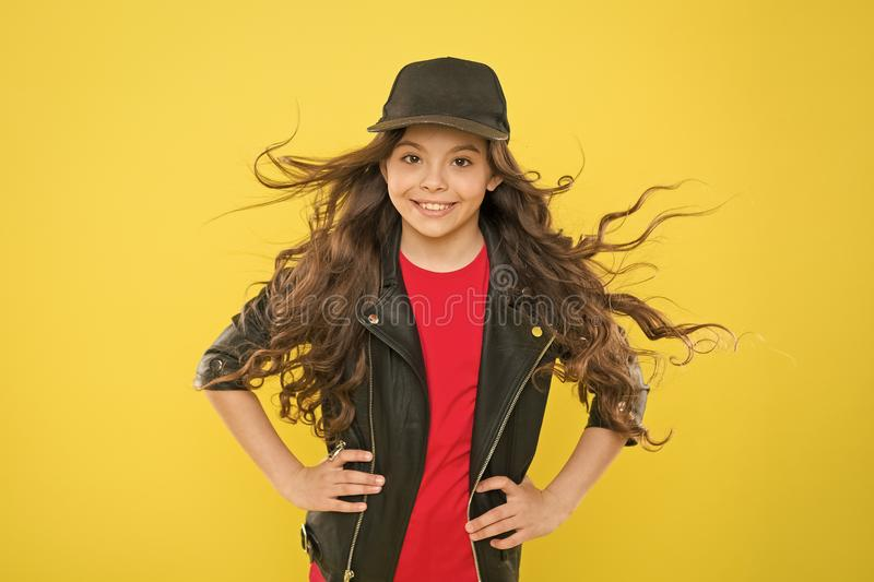 Girl adorable kid long wavy hair yellow background. Wind can also damage hair. Strong persistent winds can create stock photo