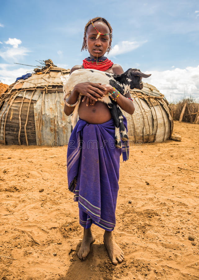 Girl from the African tribe Dasanesh holding a goat. OMO VALLEY, ETHIOPIA - MAY 6, 2015 : Girl from the African tribe Dasanesh holding a goat in her village royalty free stock photos