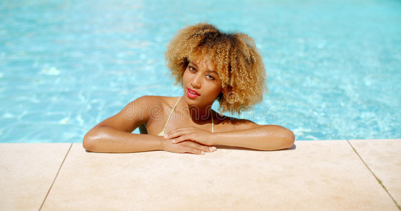 Girl With Afro Haircut Relaxing in Swimming Pool. On Slow Motion Video stock photos
