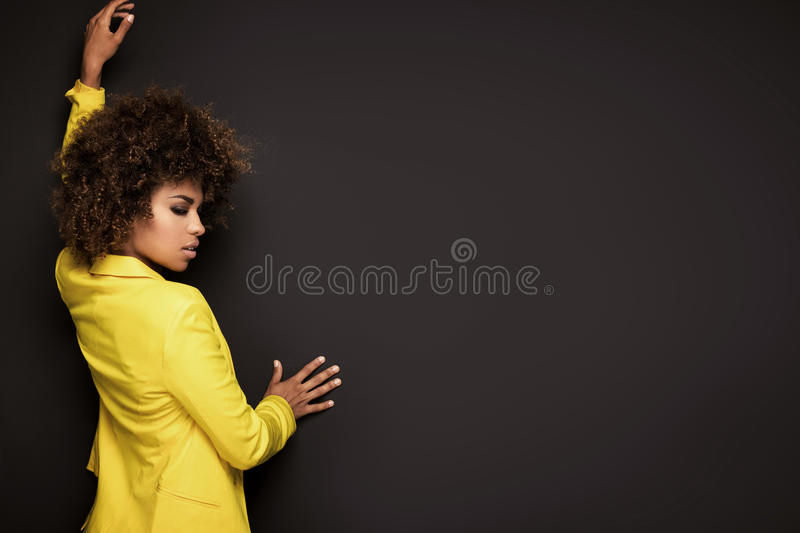Girl with afro hairstyle posing in yellow jacket. stock image
