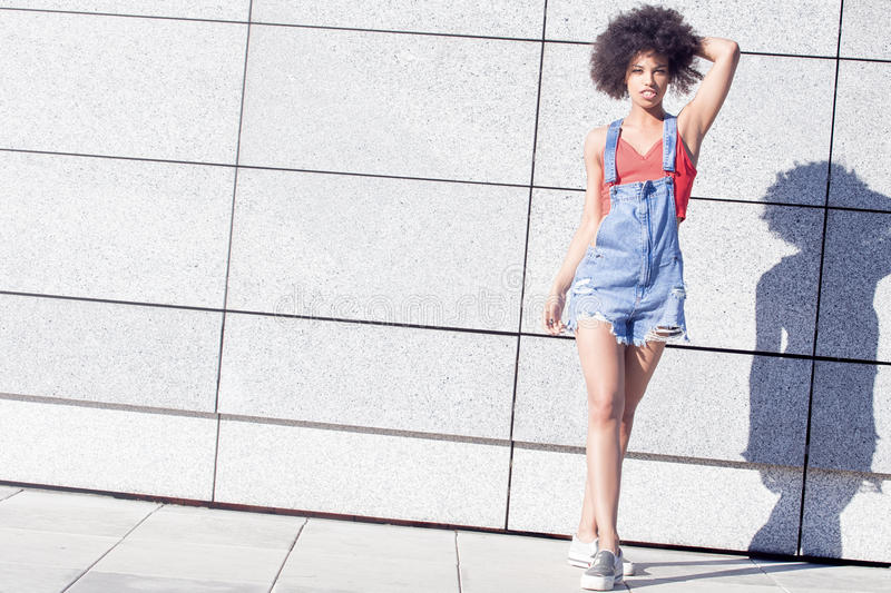 Girl with afro posing. Young girl with afro hairstyle posing on the street at sunny day royalty free stock photos