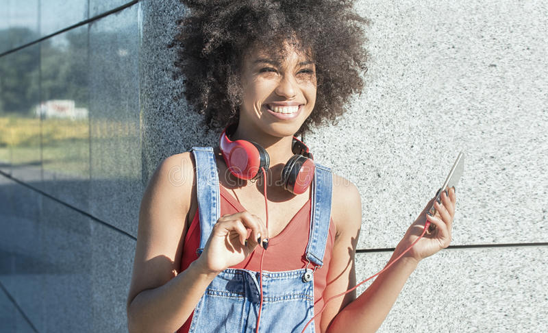 Girl with afro using mobile phone. Young african american girl using mobile phone and headphones, smiling stock photo