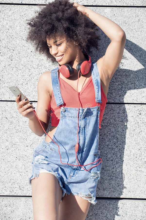 Girl with afro using mobile phone. Young african american girl using mobile phone and headphones, smiling stock images