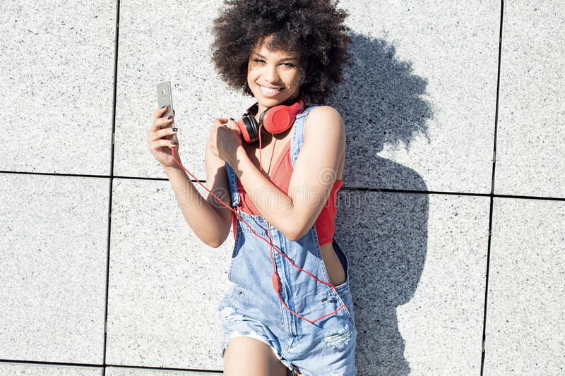Girl with afro using mobile phone. Young african american girl using mobile phone and headphones, smiling royalty free stock photography
