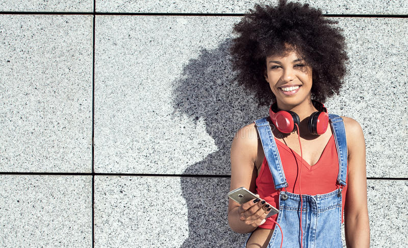 Girl with afro using mobile phone. Young african american girl using mobile phone and headphones, smiling stock photos