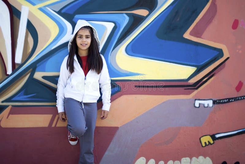 Girl against graffiti wall. Girl standing against graffiti wall royalty free stock image