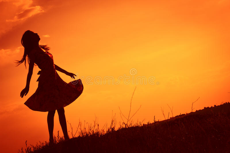 Girl against sunset skies. The silhouette of a girl with a dress against the sunset skies royalty free stock photo
