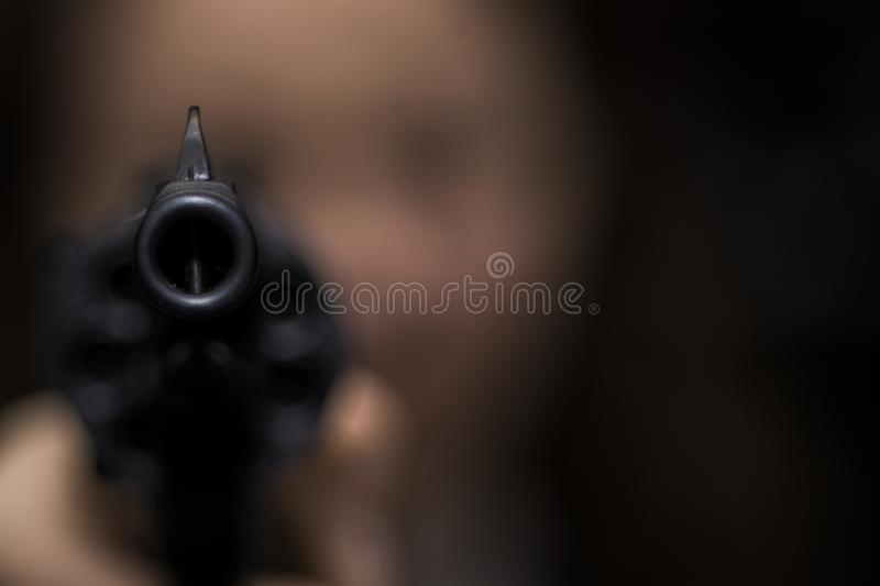The girl is aiming from the revolver. Right into the photographer. focus on the muzzle of the revolver. the girl`s face is blurry stock photo