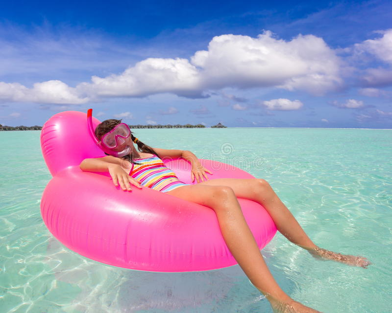 Girl on air mattress in sea. Girl with snorkel relaxing on chair shaped pink air mattress on sea, blue sky and cloudscape background stock photos