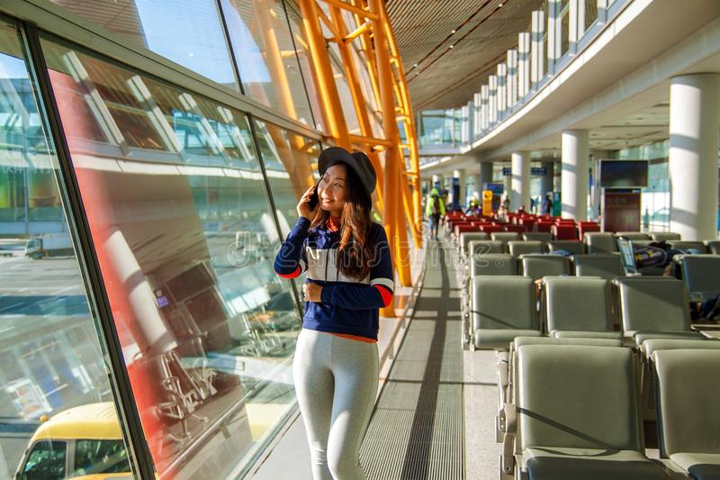 Girl at the airport window talking by phone. Asian woman using cell phone in airport, looking out window royalty free stock photos
