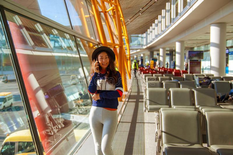 Girl at the airport window talking by phone. Asian woman using cell phone in airport, looking out window stock photo