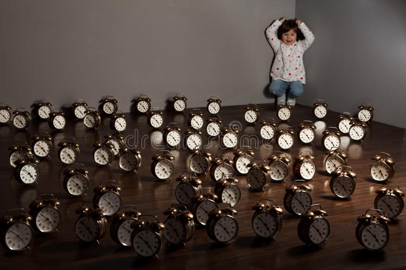 Girl with alarm clocks. A girl in the corner of a room in which the floor is covered by alarm clocks stock photo