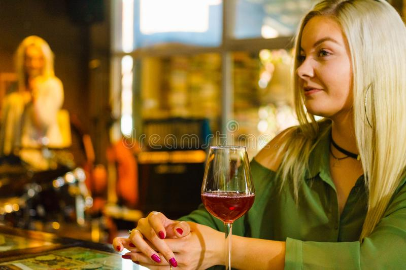 Girl with alcohol glass in pub club stock image