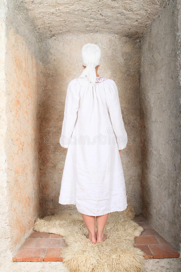 Girl in alcove. Young woman - girl in white dress and headscarf standing on fur in alcove royalty free stock photos