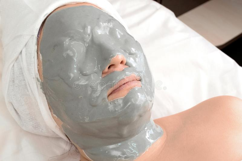 The girl in the alginate anti-wrinkle mask. Close-up of a woman lying relaxing in a beauty salon. Spa treatments at home or royalty free stock image