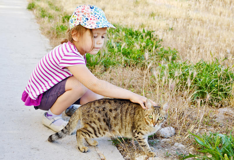 Girl and alley cat. Little girl petting alley cat on the street royalty free stock photography