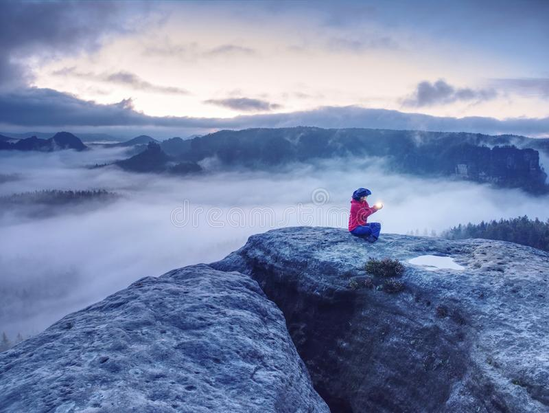 Girl alone sit on mountain summit likes ship in misty ocean royalty free stock image