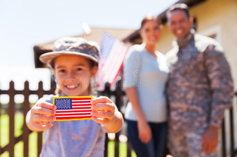 Girl american flag badge. Little girl holding american flag badge in front of parents royalty free stock photo
