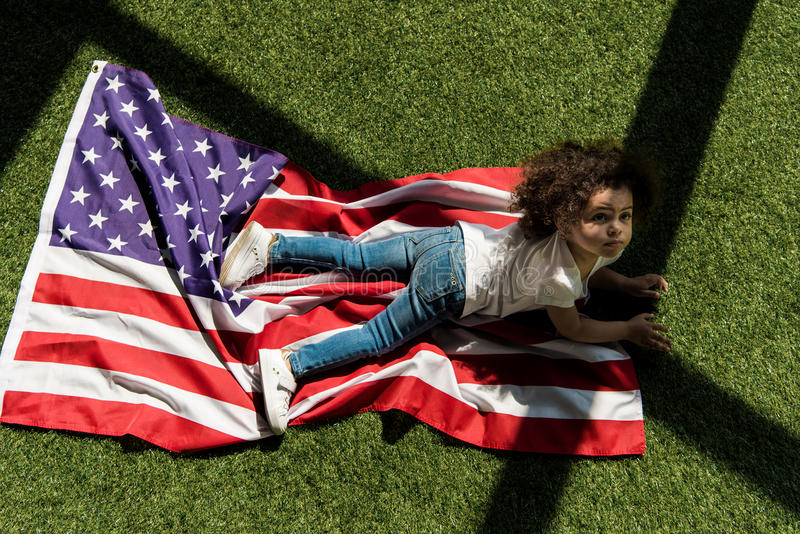 Girl with american flag on grass royalty free stock photo