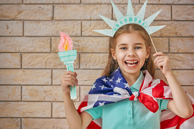 Girl with American flag. Patriotic holiday. Happy kid, cute little child girl with American flag in the room indoors. USA celebrate 4th of July stock images