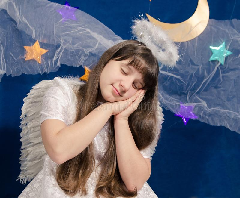 Girl in angel costume sleeps on a background of dark blue sky stock photography