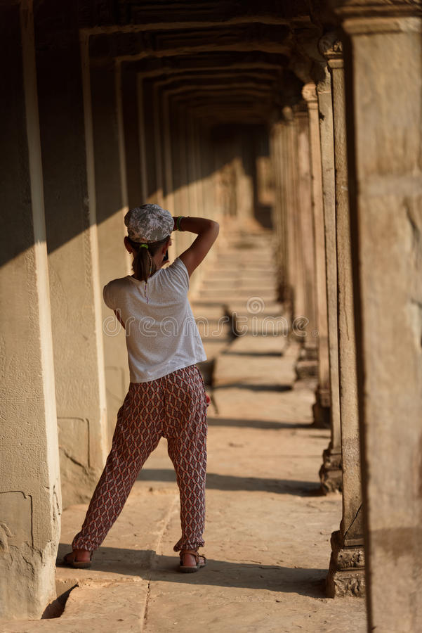 Girl in Angkor Wat, Cambodia. Young girl photographing stone walkway at Angkor Wat, Cambodia royalty free stock photography