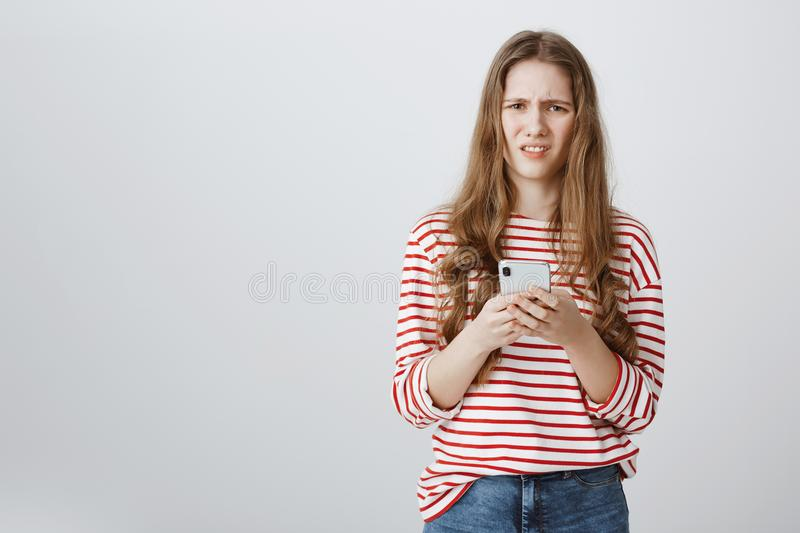 Girl is annoyed with spam on her mailbox. Portrait of bothered and confused caucasian woman holding smartphone, looking stock photo