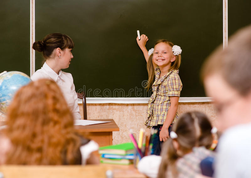 Girl answers questions of teachers near a school board royalty free stock photo