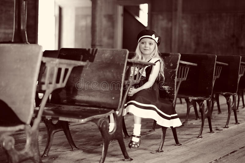 Girl at antique school desk. Young girl sitting at an antique desk in an old school classroom royalty free stock photo