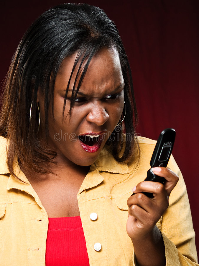 Girl Appalled While Using Cellphone. African American girl engaged in an unpleasant cellphone experience royalty free stock photo