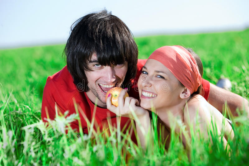 Girl With Apple And Boy On Grass Stock Photography