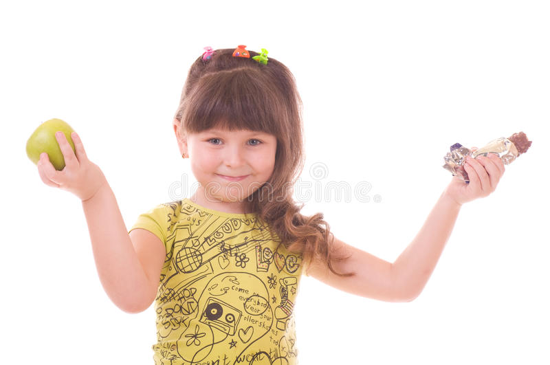 Girl with apple and chocolate. Beautiful little girl with apple and chocolate on white background stock images
