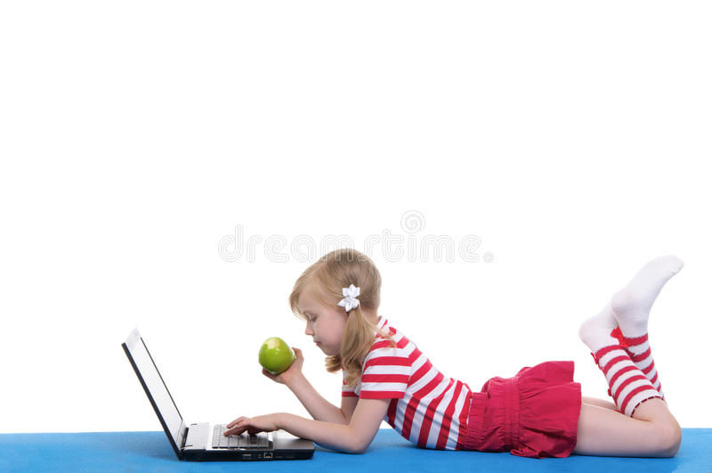 Girl with an apple and laptop on rug stock image