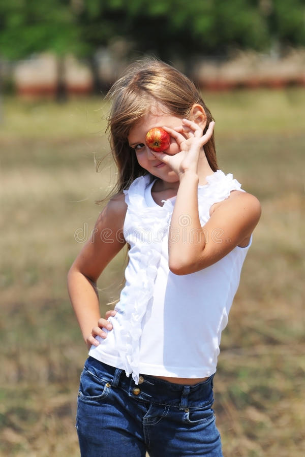 Girl with apple. Stand and looking at camera smiling royalty free stock photos