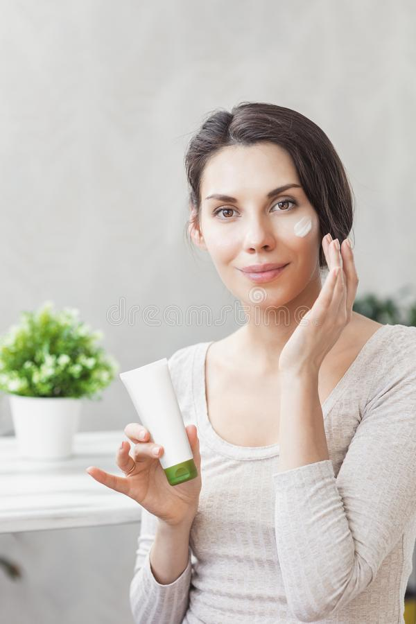 Girl applies face cream. Skin care and beauty concept. Young woman applying moisturizer on her face. Face Skin care royalty free stock image