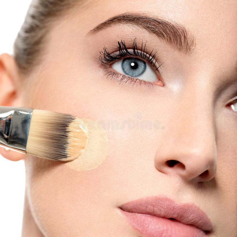 Girl applies tonal foundation on face use makeup brush royalty free stock image