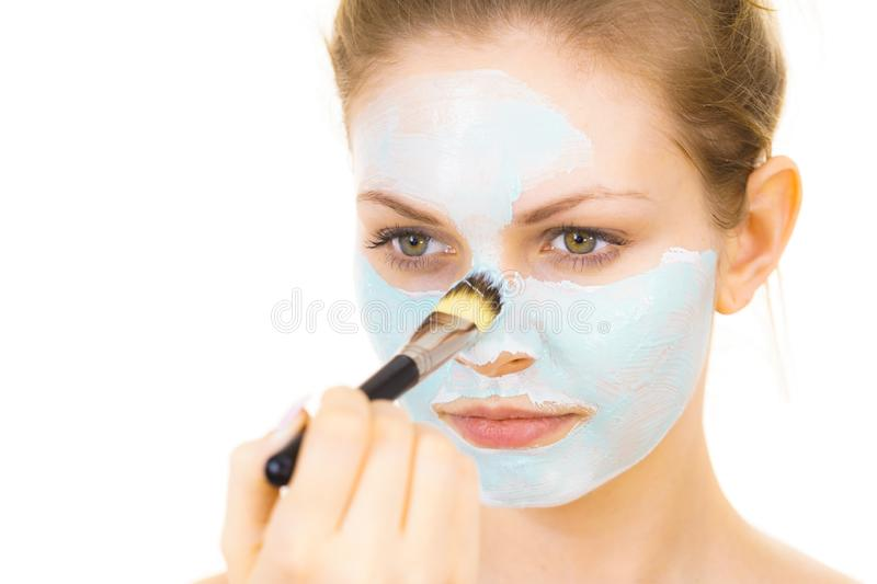 Girl apply green mud mask to face. Young woman applying with brush green mud mask to face, on white. Teen girl taking care of oily skin, purifying the pores stock images