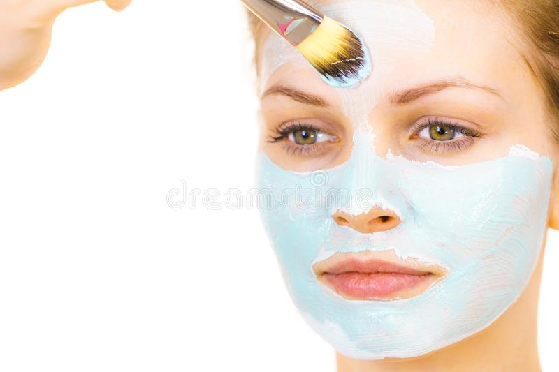 Girl apply green mud mask to face. Young woman applying with brush green mud mask to face, on white. Teen girl taking care of oily skin, purifying the pores stock image