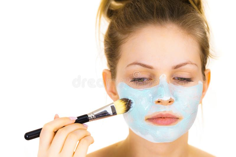 Girl apply green mud mask to face. Young woman applying with brush green mud mask to face, on white. Teen girl taking care of oily skin, purifying the pores stock photo