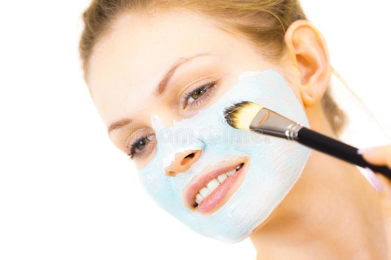 Girl apply green mud mask to face. Young woman applying with brush green mud mask to face, on white. Teen girl taking care of oily skin, purifying the pores royalty free stock image