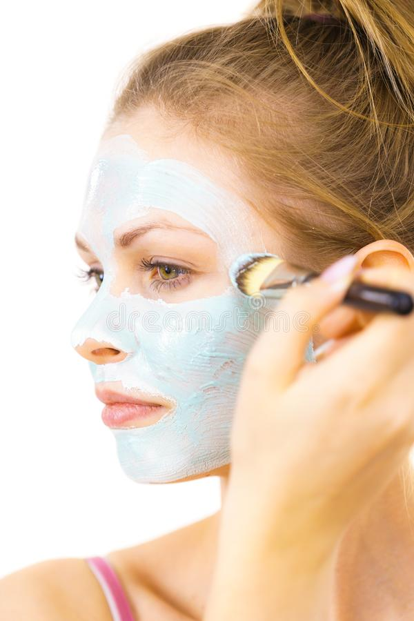 Girl apply green mud mask to face. Young woman applying with brush green mud mask to face, on white. Teen girl taking care of oily skin, purifying the pores stock photos