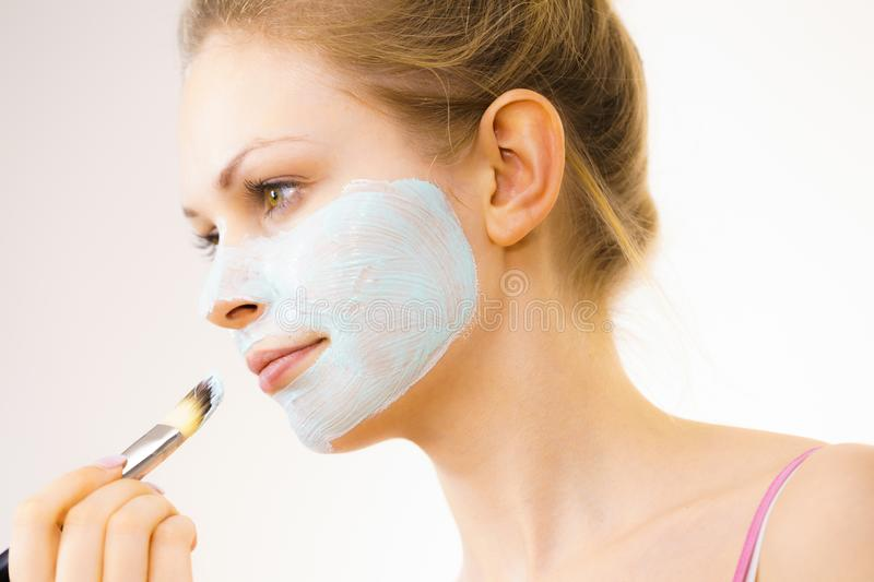 Girl apply green mud mask to face. Young woman applying with brush green white mud mask to her face. Teen girl taking care of oily skin, purifying the pores stock image