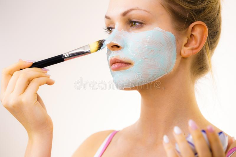 Girl apply green mud mask to face. Young woman applying with brush green white mud mask to her face. Teen girl taking care of oily skin, purifying the pores royalty free stock photo