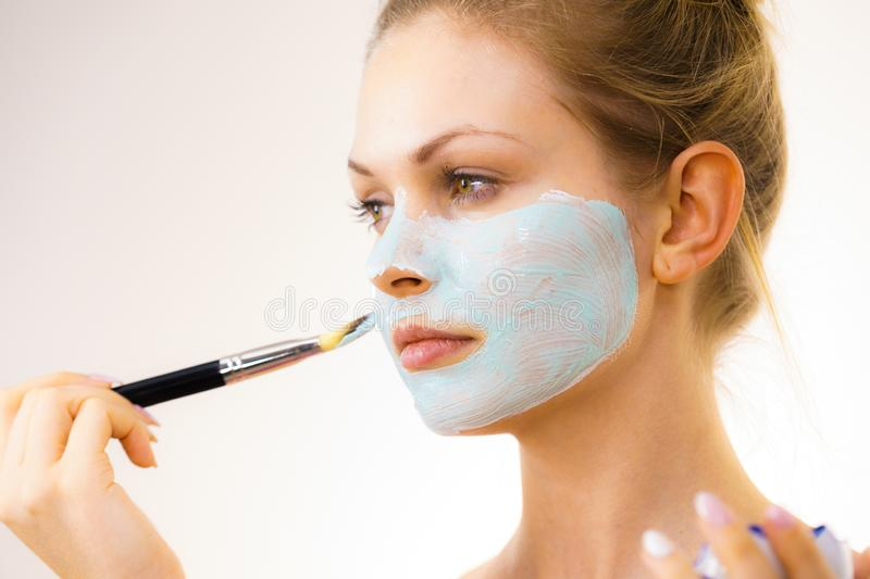 Girl apply green mud mask to face. Young woman applying with brush green white mud mask to her face. Teen girl taking care of oily skin, purifying the pores royalty free stock photos