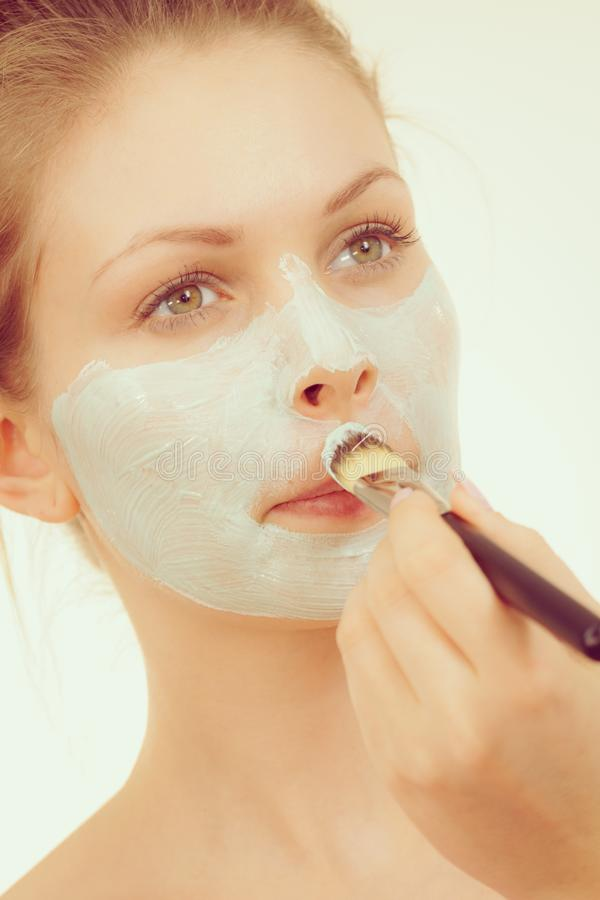 Girl apply green mud mask to face. Young woman applying with brush green white mud mask to her face. Teen girl taking care of oily skin, purifying the pores stock photos