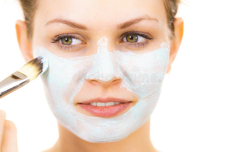 Girl apply green mud mask to face. Young woman applying with brush green mud mask to face, on white. Teen girl taking care of oily skin, purifying the pores royalty free stock photo