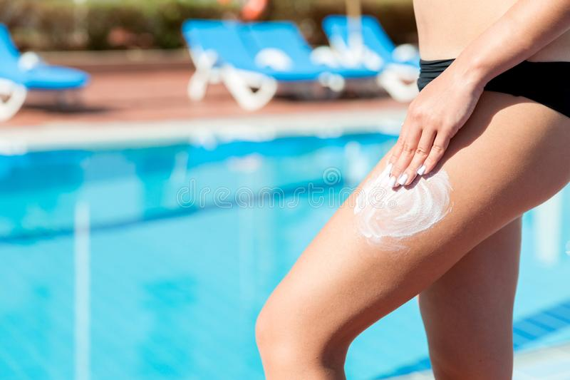 Girl apply sun protection cream with her hands on her tanned leg by pool on hot summer day. Sun Protection Factor in vacation, stock photography