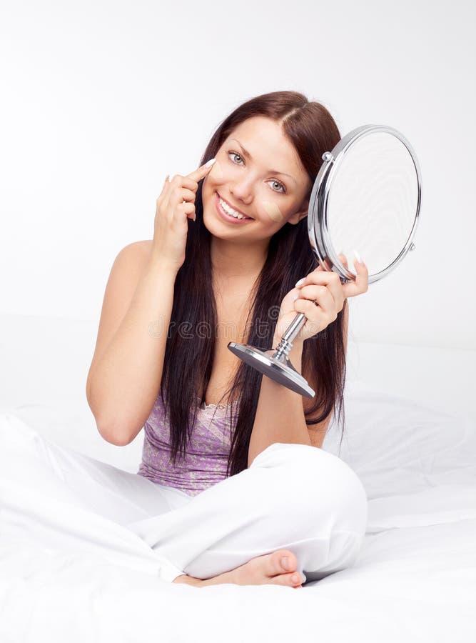 Girl applying foundation royalty free stock photos
